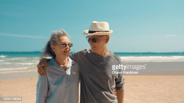 romantic senior couple walking on beautiful tropical beach. mature affectionate couple walking down sandy beach with sea behind and blue sky above - married stock pictures, royalty-free photos & images