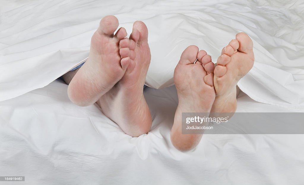 romantic senior feet under the sheets : Stock Photo