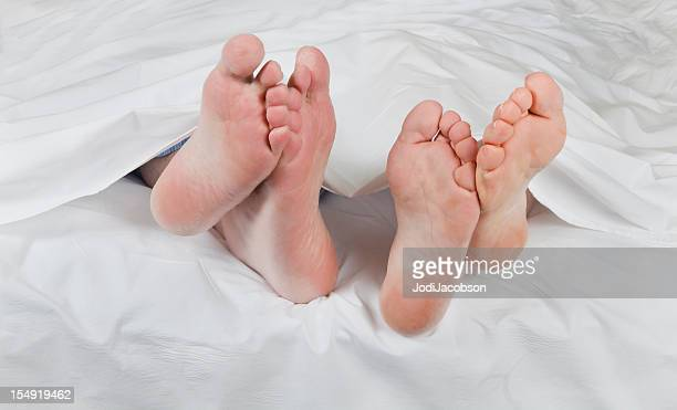 romantic senior feet under the sheets - barefoot footsie stock photos and pictures