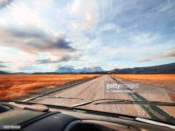 romantic sky, road, and orange grass in the mountains, view from a car - weitwinkelaufnahme stock-fotos und bilder