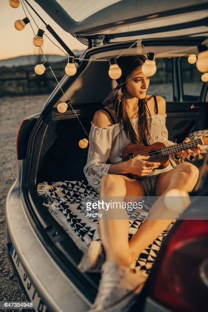 Romantic soul. Woman playing ukulele in the back of her car fild with light bubles