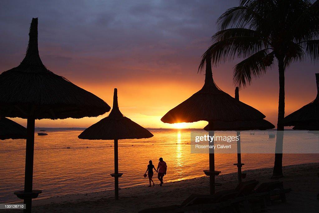 Romantic stroll at sunset on tropical beach. : Stock Photo