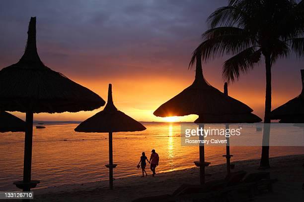 Romantic stroll at sunset on tropical beach.