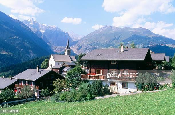 Romántico pueblo suizo con sus casas, la iglesia y a las montañas.