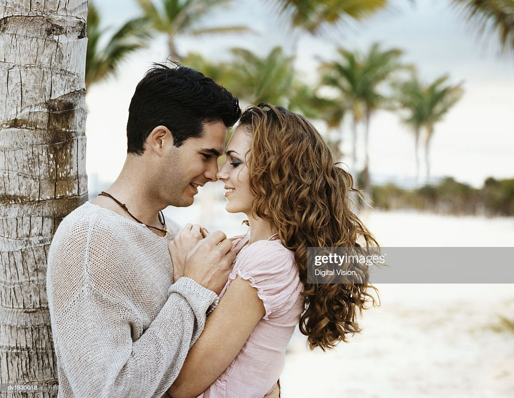 Romantic Twentysomething Couple Standing Face to Face on a Beach by a Palm Tree : Stock Photo