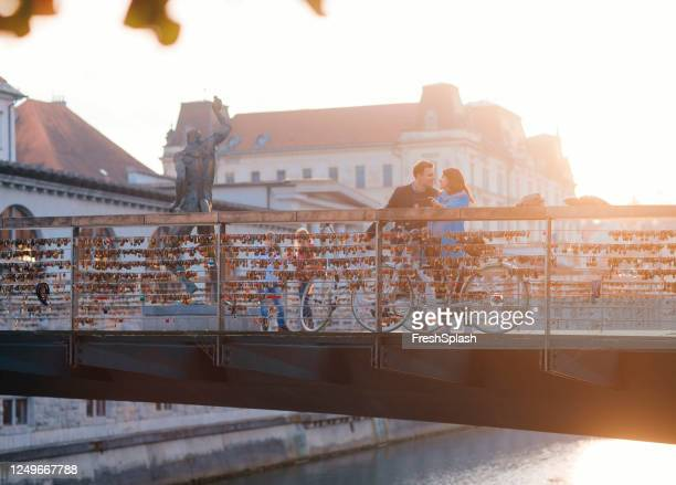 romantic vacation: couple in love standing on a bridge - slovenia stock pictures, royalty-free photos & images
