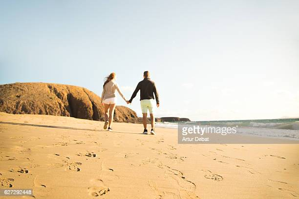 Romantic view of a couple walking on the beach holding hands in the Lanzarote island.