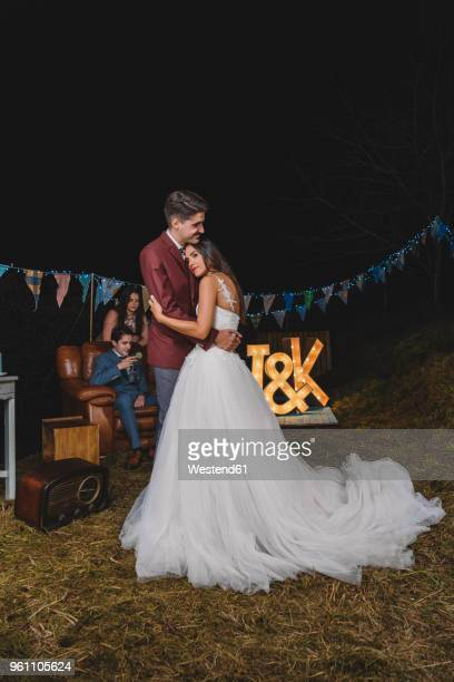Romantic wedding couple embracing on a night field party with their friends in the background