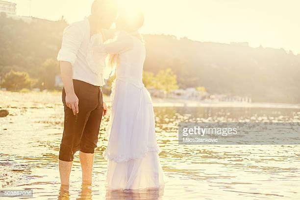 Mariage romantique couple dans la mer au coucher du soleil.