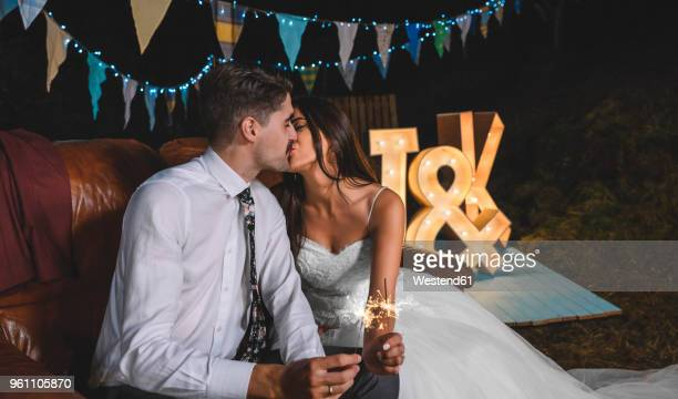 Romantic wedding couple sitting on sofa kissing while holding sparklers in their hands on a night party outdoors