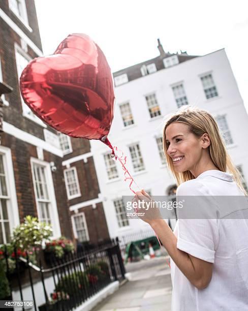 Romantic woman holding a heart shaped balloon