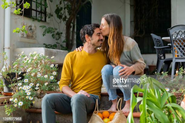 romantic woman kissing on boyfriend's forehead while sitting over steps against farmhouse - affectionate stock pictures, royalty-free photos & images