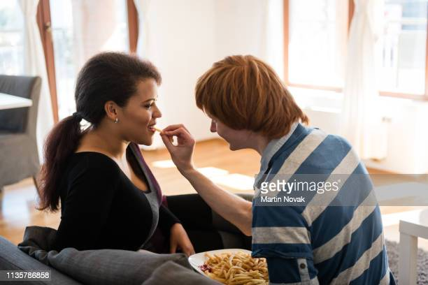 romantic young couple at home, eating french fries. - fries stock-fotos und bilder