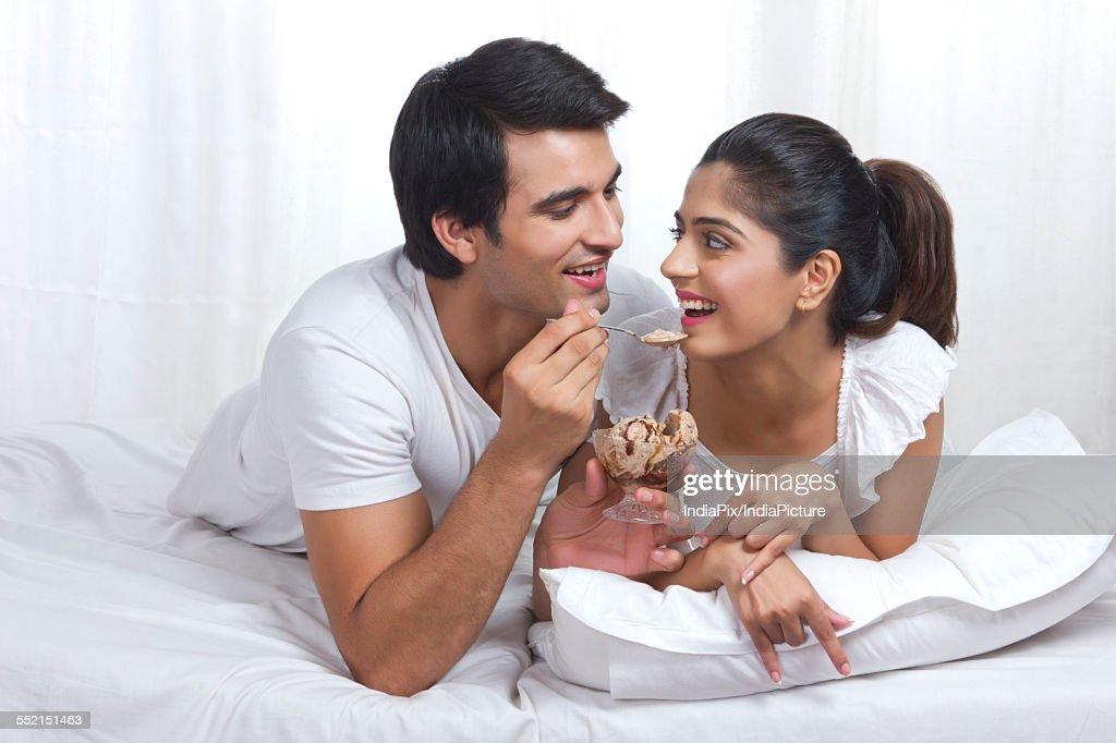 Romantic young couple enjoying chocolate ice cream in bed   Stock Photo. Romantic Young Couple Enjoying Chocolate Icecream In Bed Stock