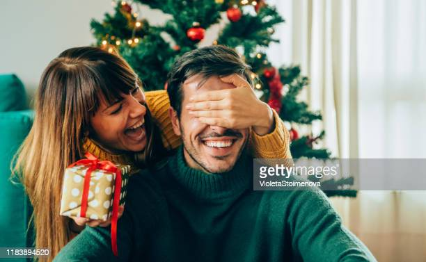 romantic young couple exchanging christmas gifts - boyfriend stock pictures, royalty-free photos & images