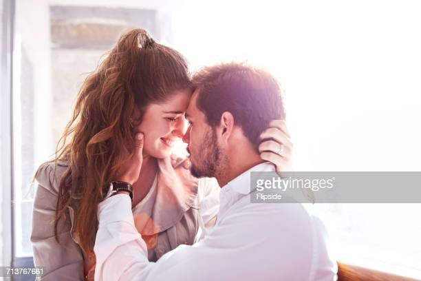 romantic young couple face to face in office - work romance stock pictures, royalty-free photos & images