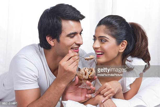 Romantic young couple having chocolate ice-cream in bed