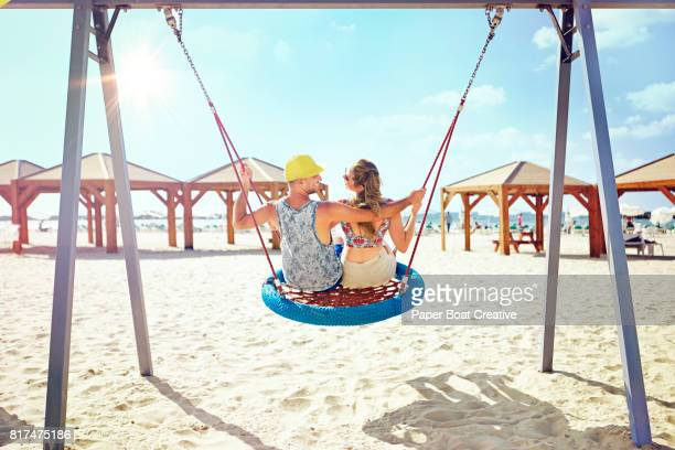Romantic young couple having fun on a blue swing at the beach on a sunny day at a resort