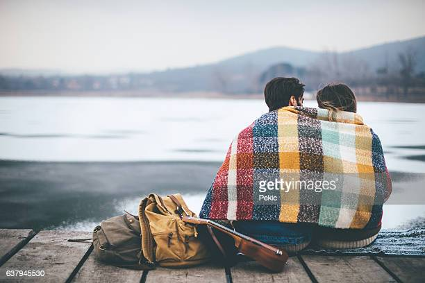 romantic young couple hugging by the lake in winter - abiti pesanti foto e immagini stock