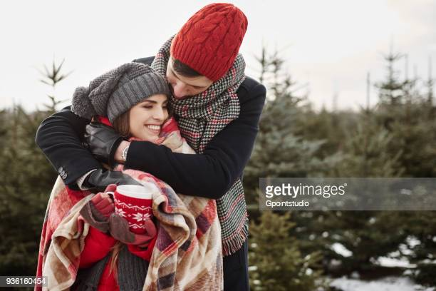 Romantic young couple in christmas tree forest wrapped in blanket