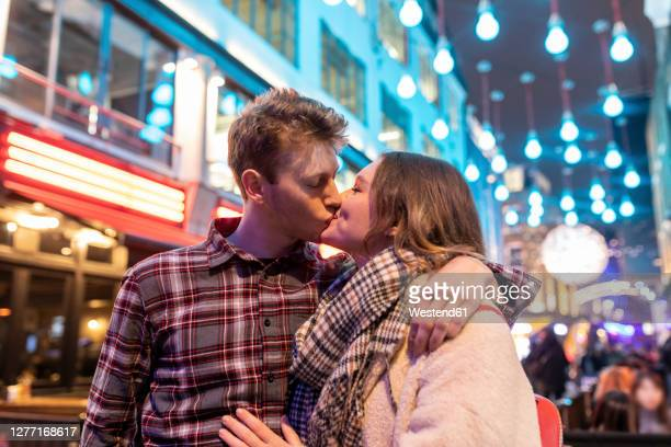 romantic young couple kissing while standing against christmas lights in city at night - kissing stock pictures, royalty-free photos & images