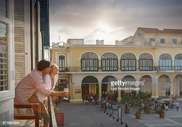 romantic young couple looking out from restaurant balcony in plaza vieja, havana, cuba - キューバ ストックフォトと画像