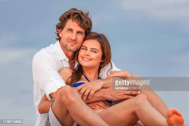 Romantic young couple lying and sunbathing on wooden wharf at sea side on holiday