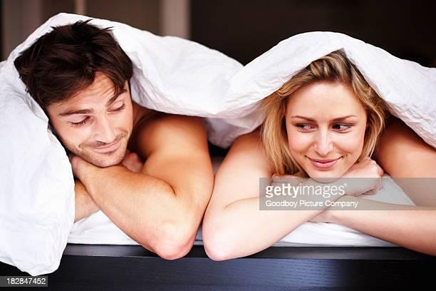 ロマンチックな若いカップルはベッドで横