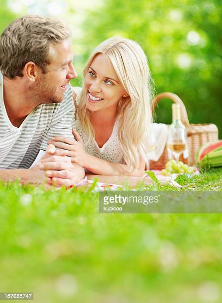 Romantic, young couple lying on grass looking at each other