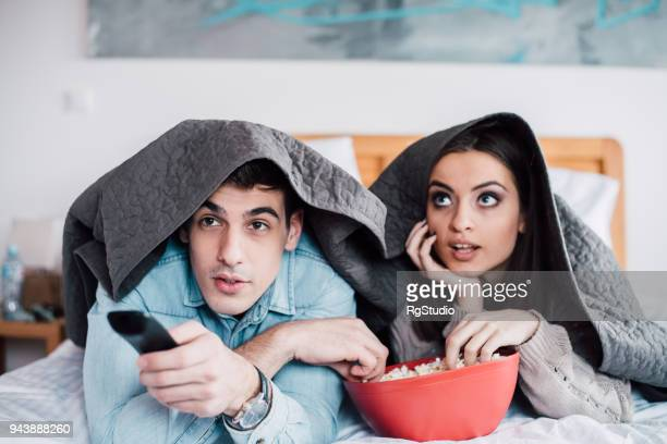 romantic young couple lying under blanket eating popcorn and watching a movie - sotto foto e immagini stock