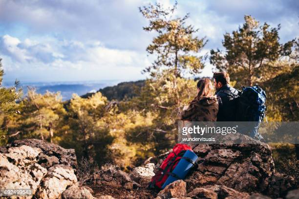 Romantic young couple of hikers sitting on the mountain peak