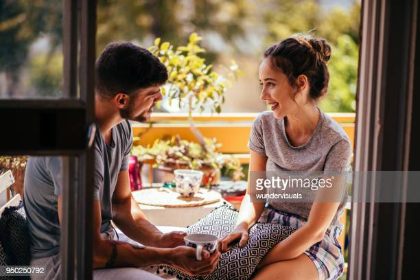 romantic young couple relaxing in the morning on apartment balcony - nightdress stock pictures, royalty-free photos & images