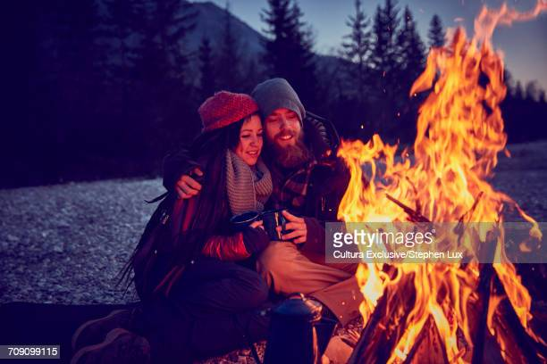 Romantic young couple sitting at campfire by River Isar, Karwendel Mountains, Bavaria, Germany