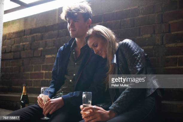 Romantic young couple sitting in bus shelter with prosecco