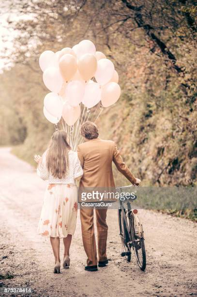 romantic young couple walking together on country road - amore foto e immagini stock