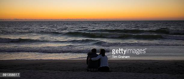 Romantic young couple watching the sunset on Captiva Island in Florida USA