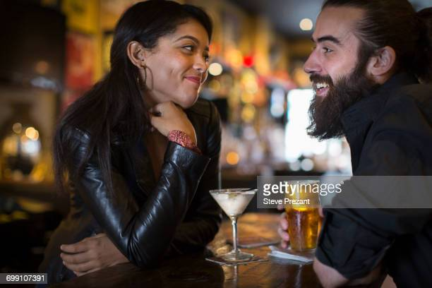 romantic young couple with cocktail and beer in public house - couples dating stock pictures, royalty-free photos & images