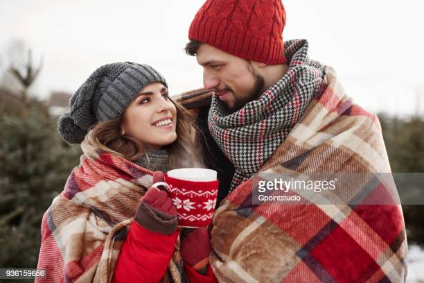 Romantic young couple wrapped in blanket while shopping for christmas tree from forest