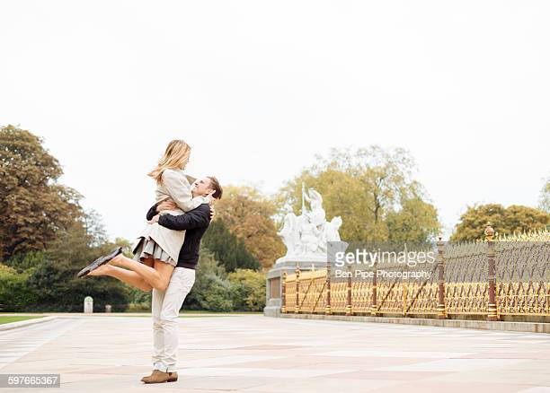 Romantic young man lifting up girlfriend in park