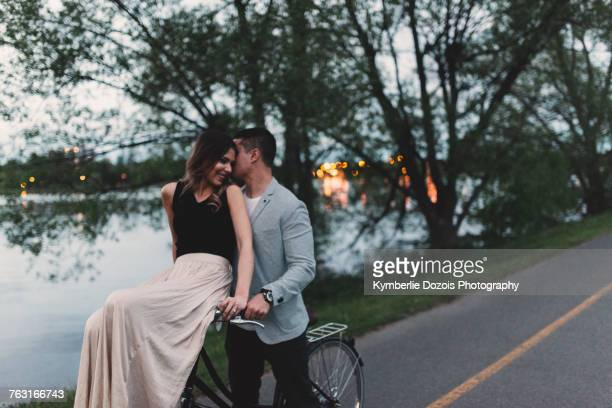 romantic young man whispering to girlfriend on bicycle handlebars by lake at dusk - robe longue photos et images de collection