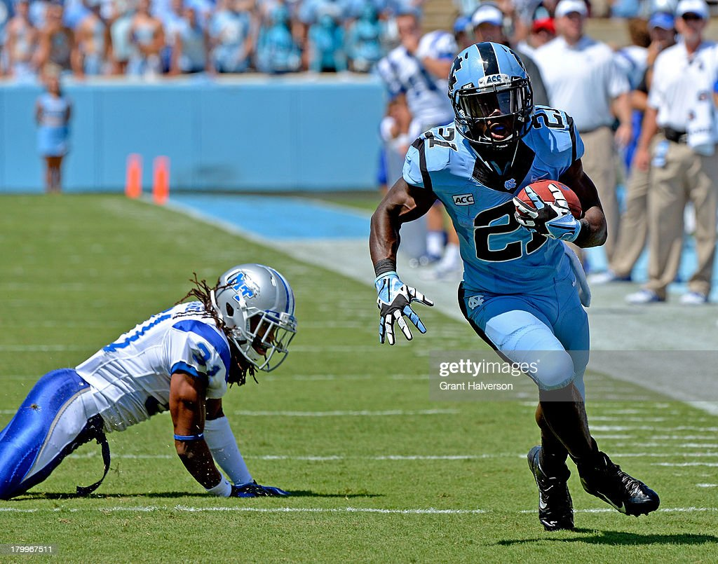 Romar Morris #21 of the North Carolina Tar Heels breaks away from Reginald Farmer #31 of the Middle Tennessee State Blue Raiders for a touchdown during the first quarter at Kenan Stadium on September 7, 2013 in Chapel Hill, North Carolina. North Carolina won 40-20.