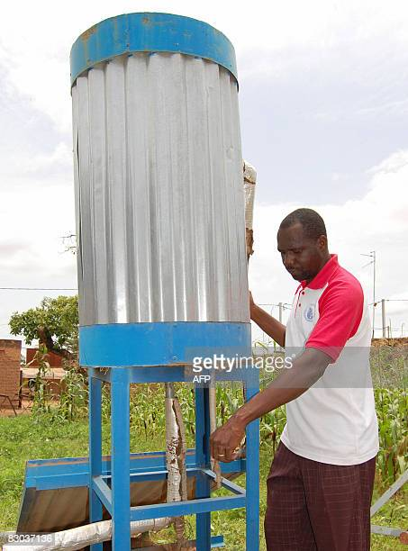 Romaric Ollo Hien A man stands by a solar panel feeding power to a water heater on a roof on September 6, 2008 in Ouagadougou. A growing number of...