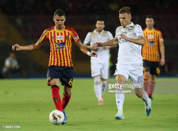 Romario Benzar of Lecce competes for the ball with Darko Lazovic of Hellas Verona during the Serie A match between US Lecce and Hellas Verona at...