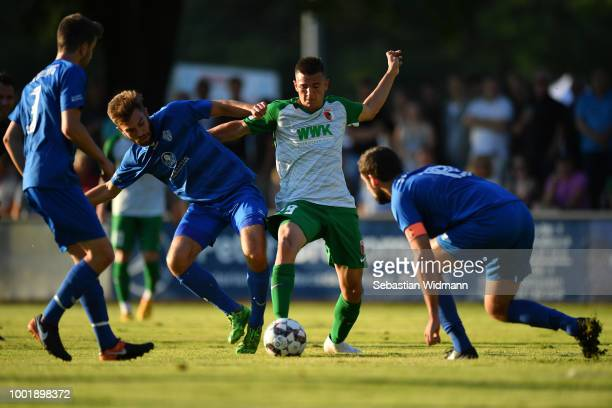 Romario Roesch of Augsburg and Paul Niehaus of Olching compete for the ball during the preseason friendly match between SC Olching and FC Augsburg on...