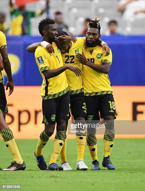 Romario Williams of Jamaica celebrates with teammates Owayne Gordon and Shaun Francis after scoring a second half goal against Canada in a...