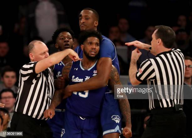 Romaro Gill of the Seton Hall Pirates holds back teammate Myles Powell as he is given a technical during an altercation with Marquette Golden Eagles...