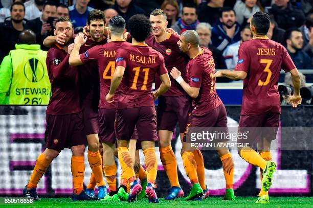 Romas Argentinean defender Federico Fazio celebrates with teammates after scoring a goal during the Europa League round of 16 first leg football...