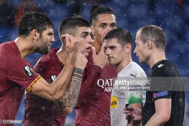 AS Roma's Argentinian defender Federico Fazio and AS Roma's Italian defender Gianluca Mancini argue with Scottish referee William Sean Collum after...