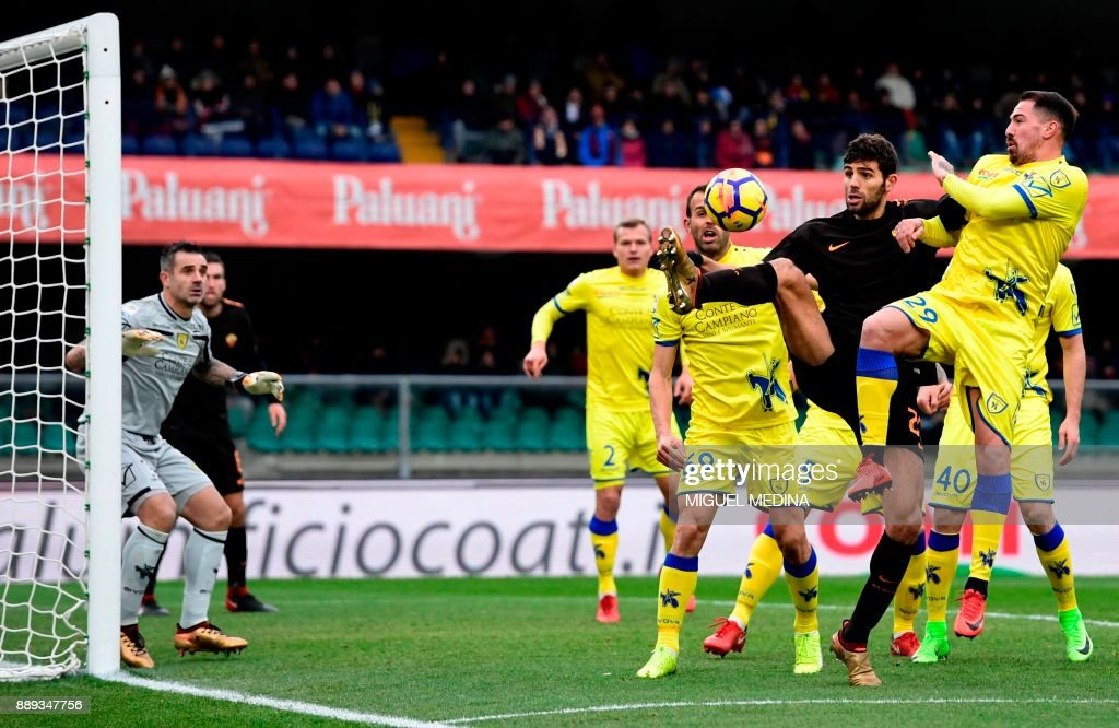 Roma's Argentinian defender Federico Fazio vies with Chievo's Italian defender Fabrizio Cacciatore during the Italian Serie A football match between AC Chievo and AS Roma at the Bentegodi stadium in Verona on December 10, 2017. /