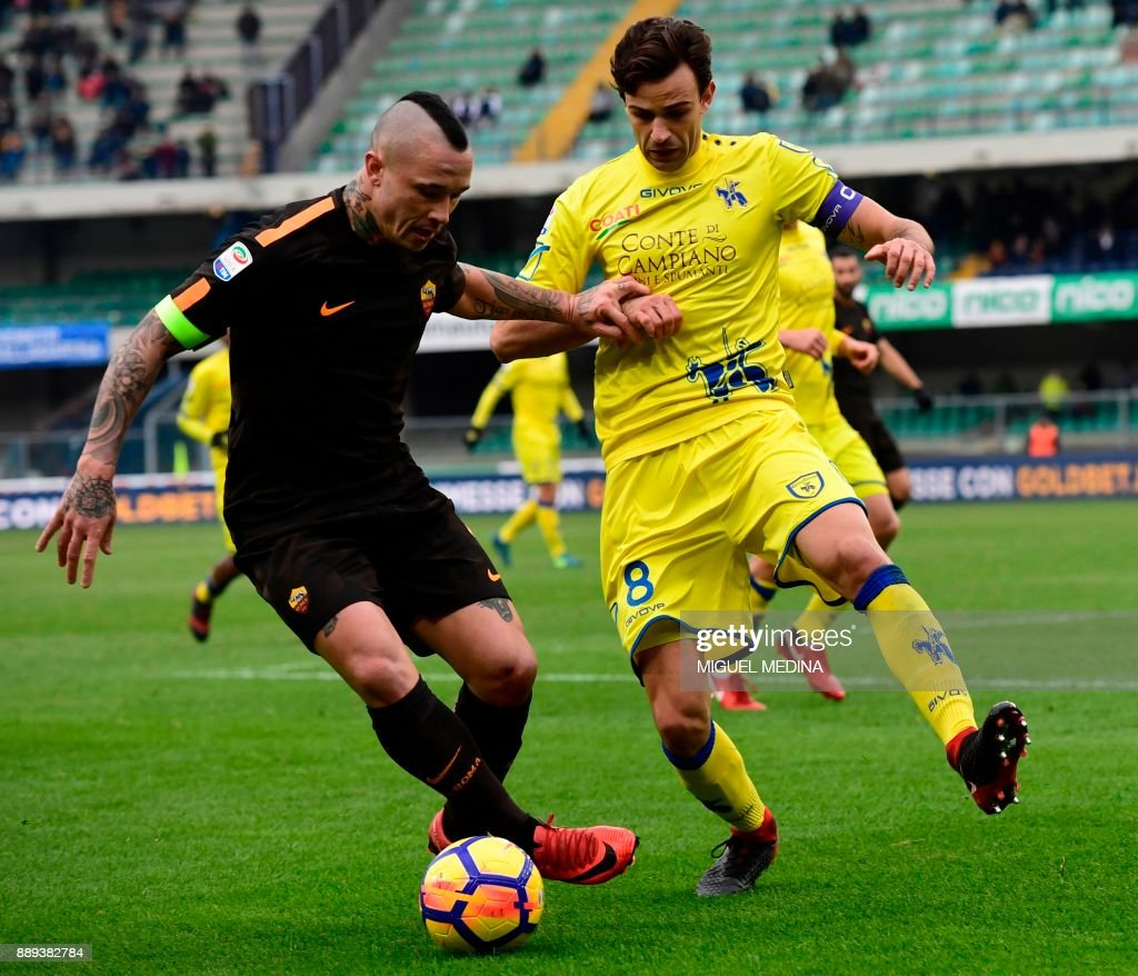 Roma's Belgian midfielder Radja Nainggolan vies with Chievo's Serbian midfielder Ivan Radovanovic during the Italian Serie A football match between AC Chievo and AS Roma at the Bentegodi stadium in Verona on December 10, 2017. /